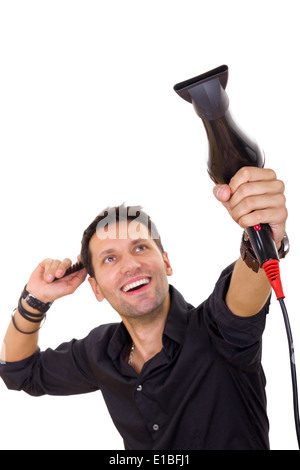 attractive smiling hairdresser using blow dryer and comb - Stock Photo