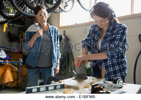 Mother and daughter woodworking in garage - Stock Photo