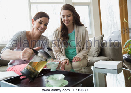 Mother and daughter pouring tea in living room - Stock Photo