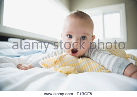 Portrait of yawning baby on bed - Stock Photo