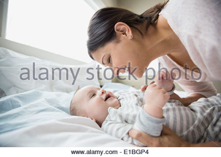 Mother and baby on bed - Stock Photo