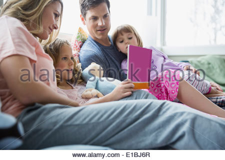 Family reading book on bed - Stock Photo