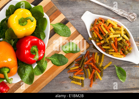 Ingredients for a delicious fusilli pasta with an overhead view of fresh colorful sweet bell peppers in red yellow - Stock Photo