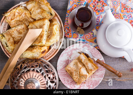View from above of a serving of delicious picnic eats with slices of borek on an authentic domed plate and Turkish - Stock Photo
