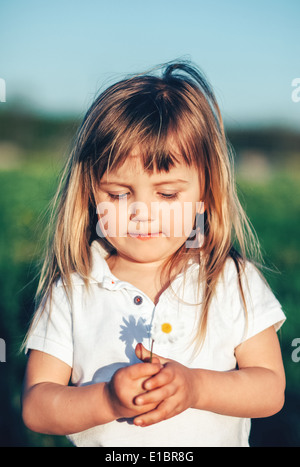 Baby girl holding little flower - Stock Photo