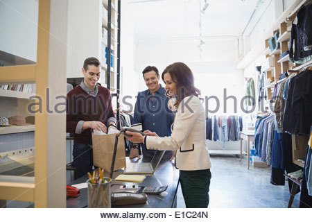 Woman using credit card machine in clothing shop - Stock Photo
