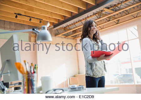 Businesswoman talking on cell phone in new office - Stock Photo