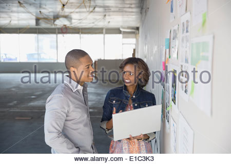 Business people with laptop brainstorming in new office - Stock Photo