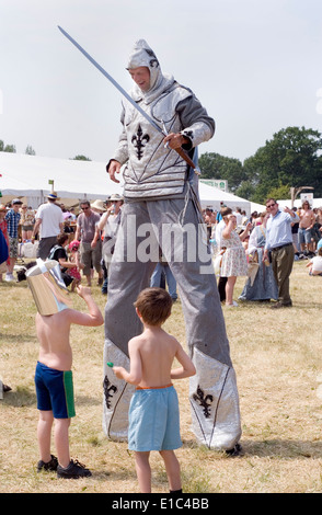 Tewkesbury Medieval Festival, Gloucester UK July 2013: Knight on stilts entertains two young boys - Stock Photo