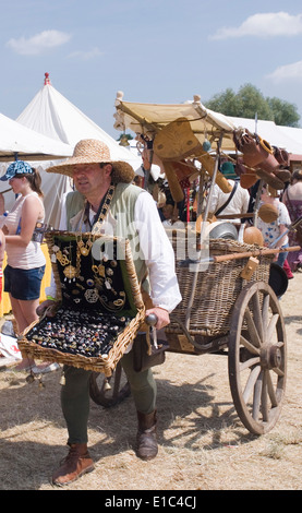 Tewkesbury Medieval Festival, Gloucester UK July 2013: pedlar with wicker & wood barrow sells his wares at the market - Stock Photo