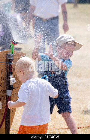 Tewkesbury Medieval Festival, Gloucester UK July 2013: children cooling off playing in water spray on a very hot - Stock Photo
