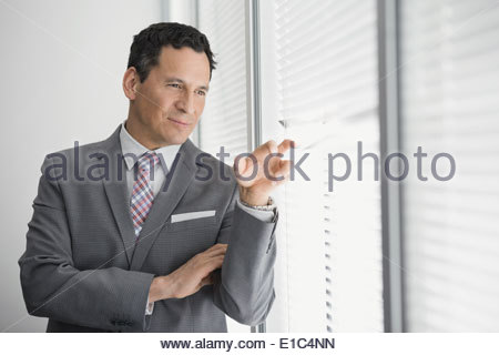Businessman peering through blinds of office window - Stock Photo