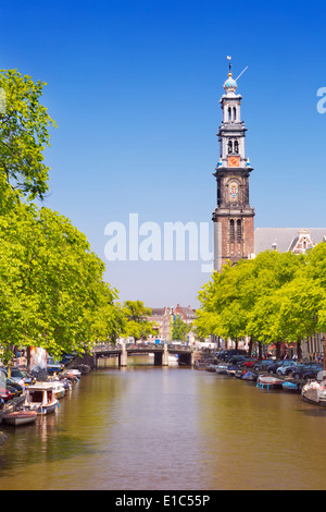 A canal and the Westerkerk church tower in Amsterdam, The Netherlands on a beautiful sunny day - Stock Photo