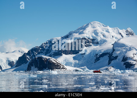 A small boat floating on the ocean among ice floes, off the shore of an island in Antarctica. - Stock Photo