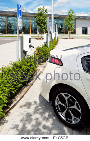 An electric auto is charging up while parked in a space marked 'Nur für Elektrofahrzeuge' at a large garden store - Stock Photo