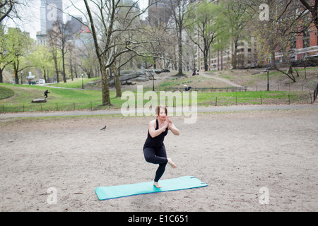 A young woman in Central Park, in a black leotard and leggings, doing yoga. - Stock Photo