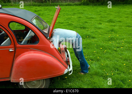 A  person leaning in to the boot at the rear of the car. - Stock Photo