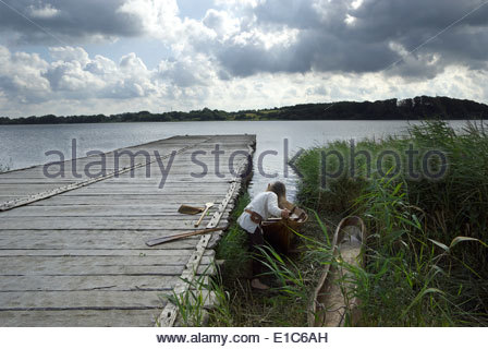 A man wearing traditional Viking costume pushes a canoe into the Haddebyer Noor, the bay at the west end of the - Stock Photo