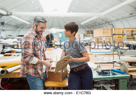 Workers with clipboard in textile manufacturing plant - Stock Photo