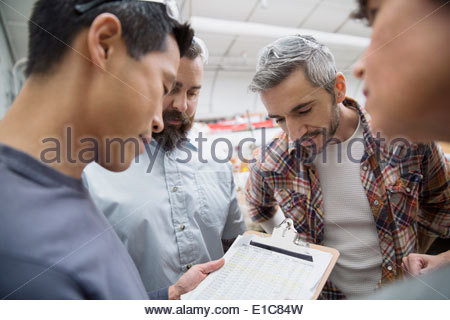 Workers with clipboard meeting in textile manufacturing plant - Stock Photo