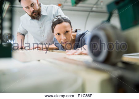 Workers using machinery in textile manufacturing plant - Stock Photo