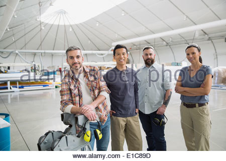 Portrait of smiling workers in textile manufacturing plant - Stock Photo