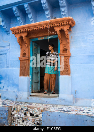 India, Rajasthan, Jodhpur, young woman in doorway of blue painted property - Stock Photo