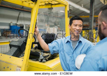 Workers talking at forklift in factory - Stock Photo