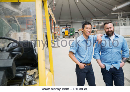 Portrait of workers near forklift in manufacturing plant - Stock Photo