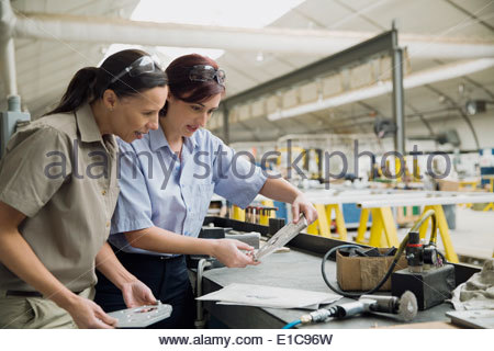 Workers examining metal part in manufacturing plant - Stock Photo