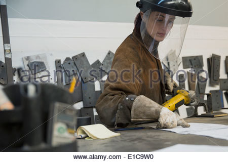 Female welder in manufacturing plant - Stock Photo