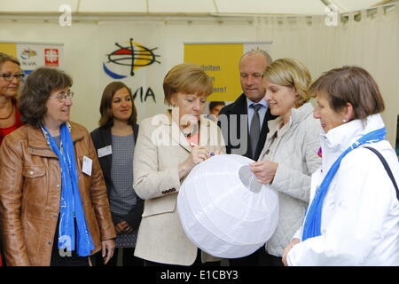 The German Chancellor Angela Merkel signs a chinese lantern with a message to the young people at the stall of the - Stock Photo