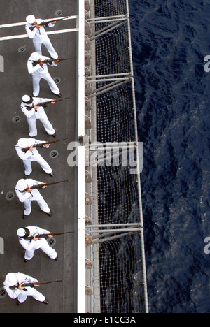 U.S. Sailors render a rifle salute during a burial at sea ceremony aboard the aircraft carrier USS Nimitz (CVN 68) - Stock Photo