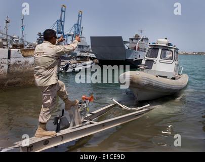 U.S. Navy Master-at-Arms 1st Class Pedro Rocha, a member of the harbor patrol unit at Camp Lemonier, Djibouti, guides - Stock Photo