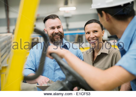Workers talking at forklift - Stock Photo