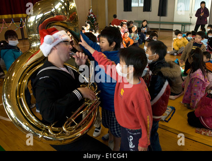 U.S. Navy Musician 2nd Class James Brownell, of the U.S. 7th Fleet brass band, performs for children during a holiday - Stock Photo