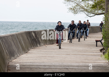 Scenic view from the boardwalk along Lake Ontario on Ward's Island on Toronto Islands with cyclists. - Stock Photo