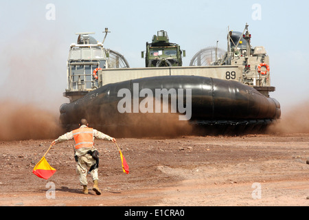 A U.S. service member directs a landing craft, air cushion carrying Marines and equipment onto the beach in Djibouti - Stock Photo