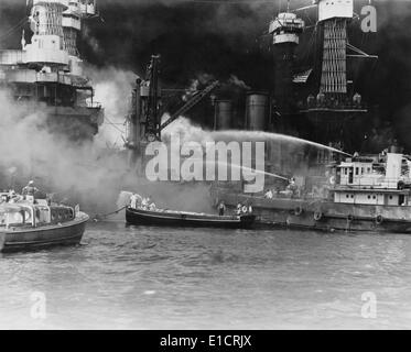U.S. sailors in fireboats at the side of the burning battleship, USS West Virginia. The ship was struck by at least - Stock Photo