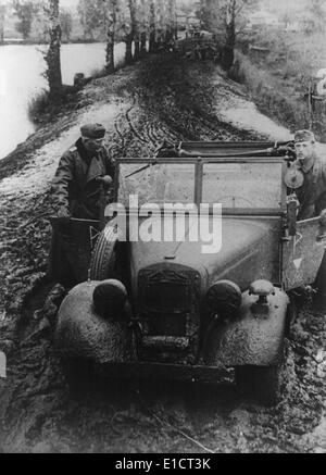 German soldier and officer pushing their car through Russian mud. In fall 1941, the semiannual Russian mid season - Stock Photo