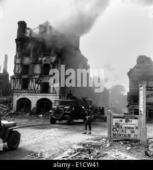 Canadian soldier controls traffic in burning Falaise ruins on August 17, 1944. A truck towing an anti-aircraft gun - Stock Photo