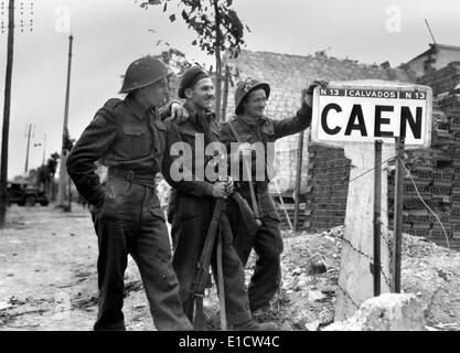 Canadian soldiers at a sign for the port city of Caen, their first critical Post D-Day objective. July 9, 1944. - Stock Photo