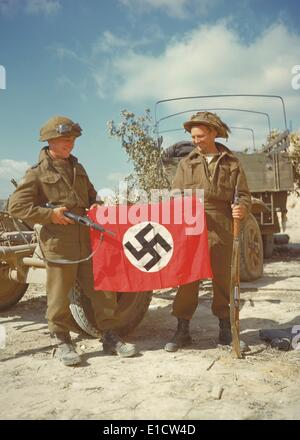 Canadian soldiers with a Nazi flag captured in Haut-Mesnil. August 10, 1944. Normandy, France, World War 2. (BSLOC - Stock Photo