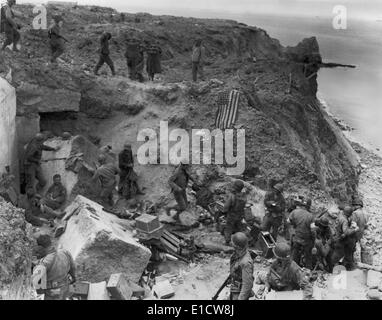 German prisoners captured by U.S. Rangers on Pointe du Hoc, during D-Day Invasion. The American flag signals the - Stock Photo