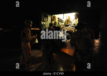 U.S. Air Force pararescuemen assigned to the 79th Expeditionary Rescue Squadron and German medics load a wounded - Stock Photo