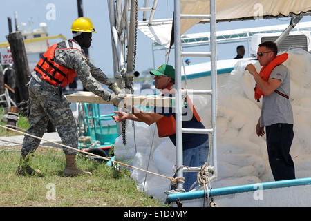U.S. Soldiers from the Louisiana Army National Guard load oil spill boom materials onto local fishing boats at the - Stock Photo