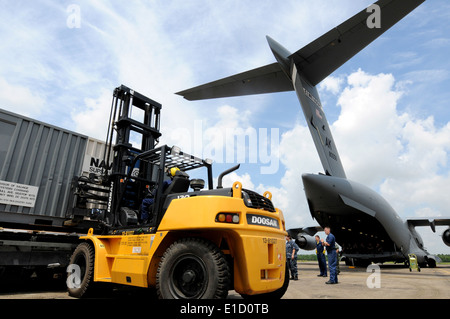 U.S. Sailors remove oil spill containment equipment from a U.S. Air Force C-17 Globemaster III aircraft at Naval - Stock Photo