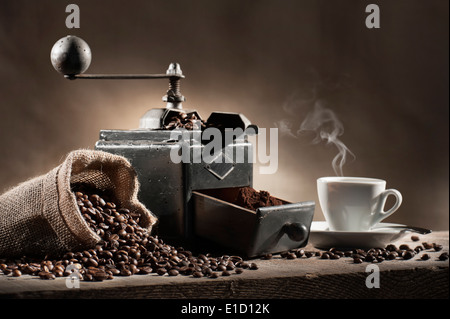 coffee beans in jute bag with coffee grinder and hot cup of coffee on wooden table - Stock Photo