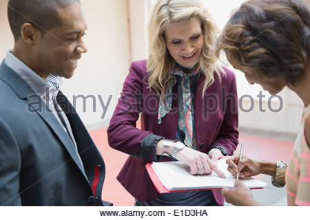 Business people signing contract in new office - Stock Photo