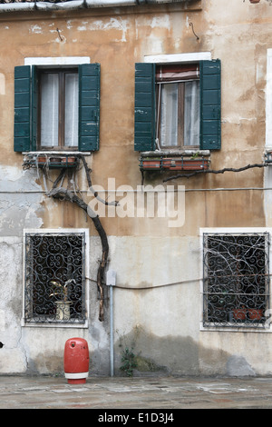 Facade of typical building facade in Venice with windows with green shutters and a red fire hydrant in front of - Stock Photo